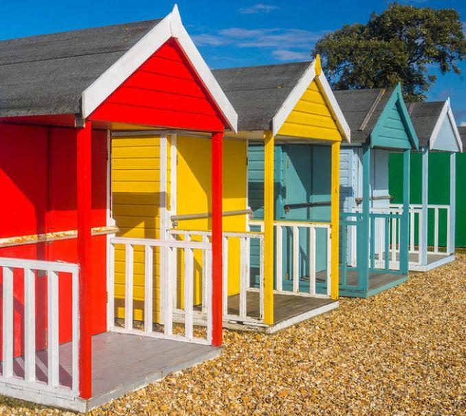 brightly coloured beach huts on pebble beach Calshot Hampshire