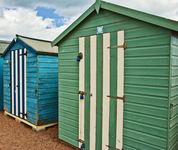 green beach hut with striped white door, teignmouth