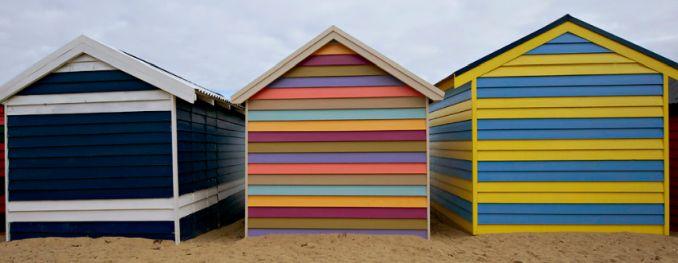 row of three multicoloured beach huts melbourne