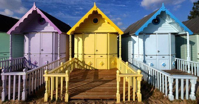 three pastel coloured beach huts on the sand