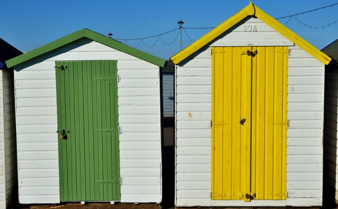 white sheds with green and yellow door paignton